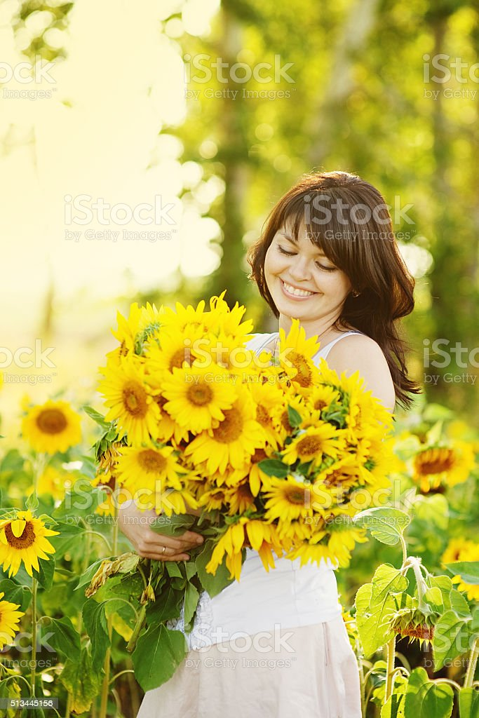 Beautiful woman with a bouquet of sunflowers stock photo