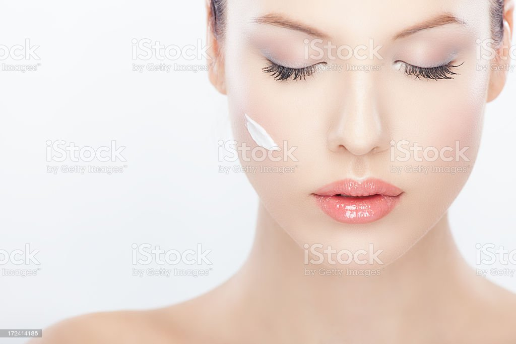 A beautiful woman with a dash of white cream on her face royalty-free stock photo