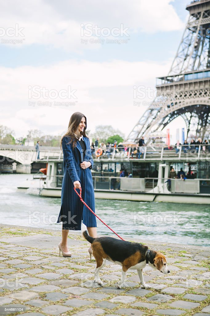 Beautiful Woman With A Dog By The Seine River stock photo