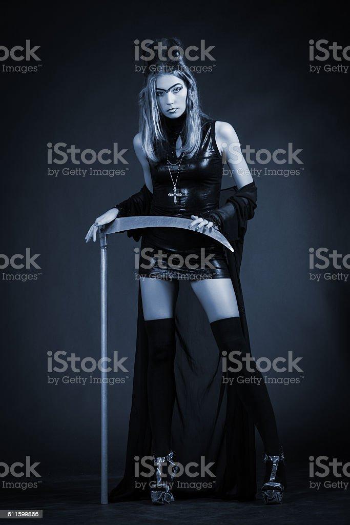 Beautiful woman with a scythe low key portrait stock photo