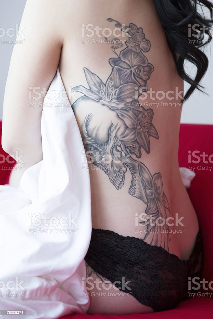 Beautiful woman with back tattoo sitting on red couch royalty-free stock photo