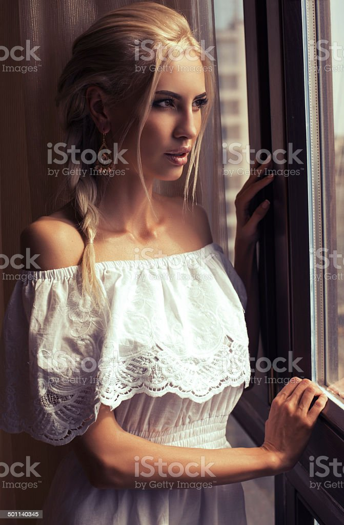 Beautiful woman with blond hair dreaming beside a window stock photo