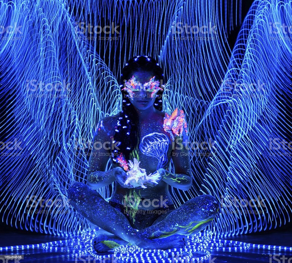 Beautiful woman with body art glowing in ultraviolet light stock photo