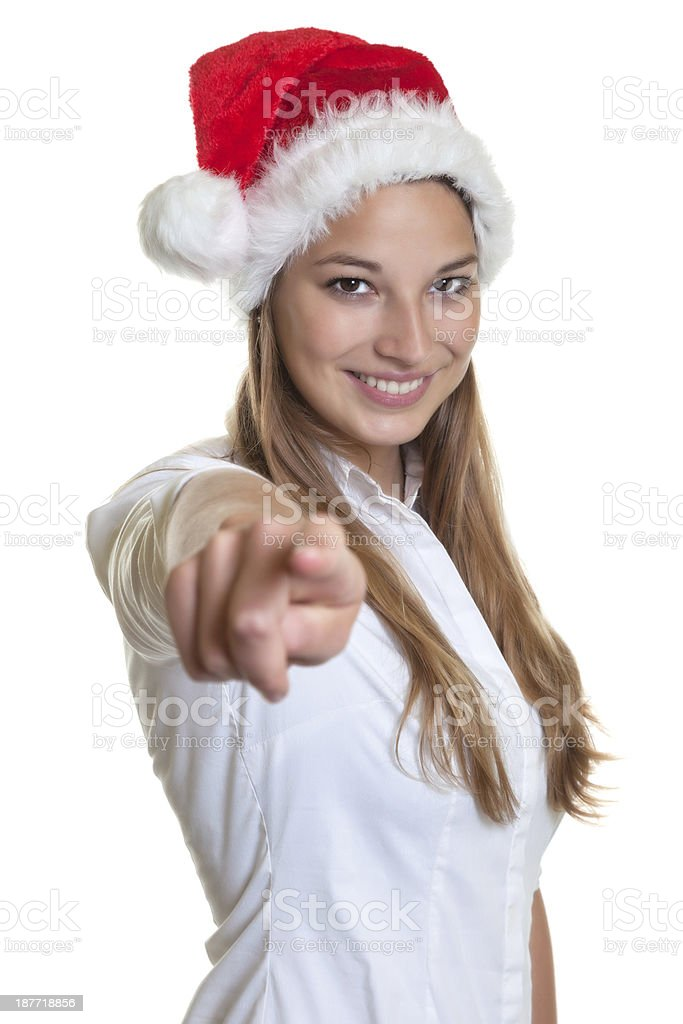 Beautiful woman with christmas hat pointing at camera royalty-free stock photo