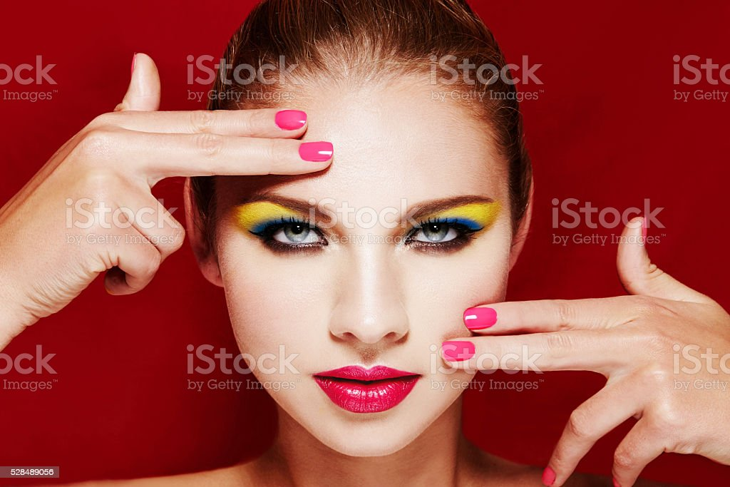 Beautiful woman with colorful makeup. pink manicure and lips. stock photo