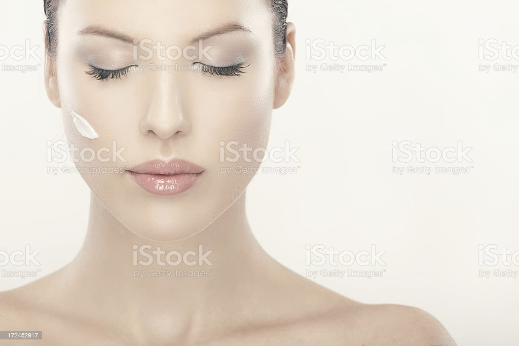 Beautiful woman with cream on her face royalty-free stock photo