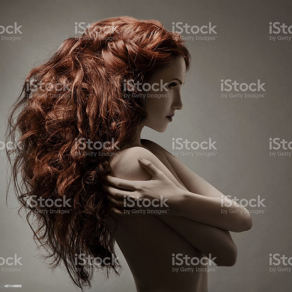 Beautiful woman with curly hairstyle against gray background stock photo