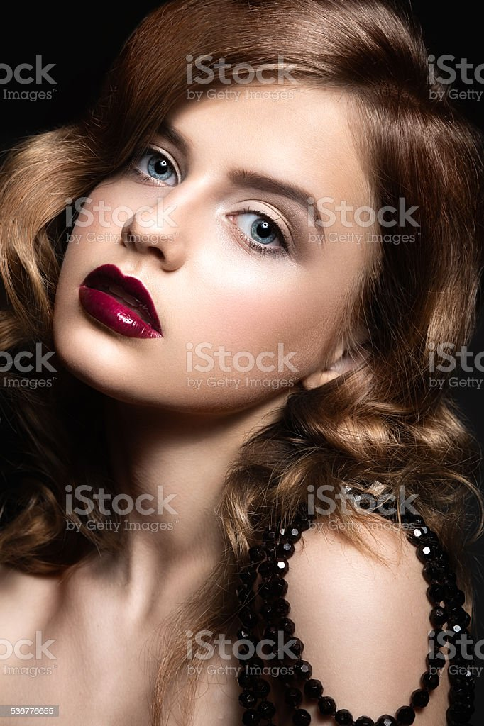 Beautiful woman with evening make-up, red lips and curls. stock photo