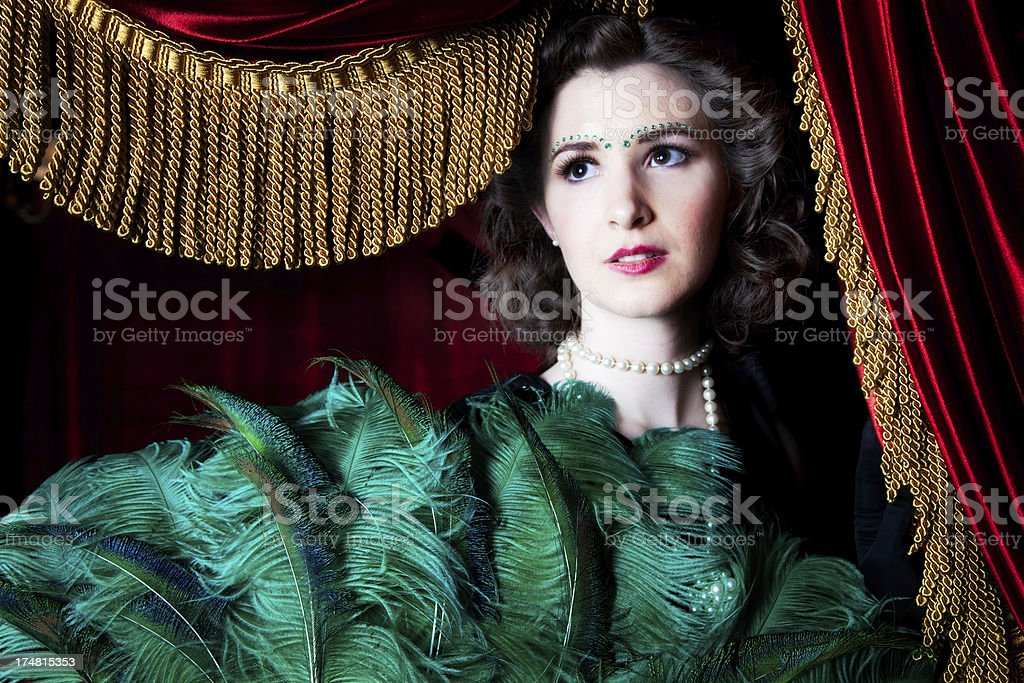 Beautiful Woman with Feathered Fan and Red Curtain Gold Fringe royalty-free stock photo