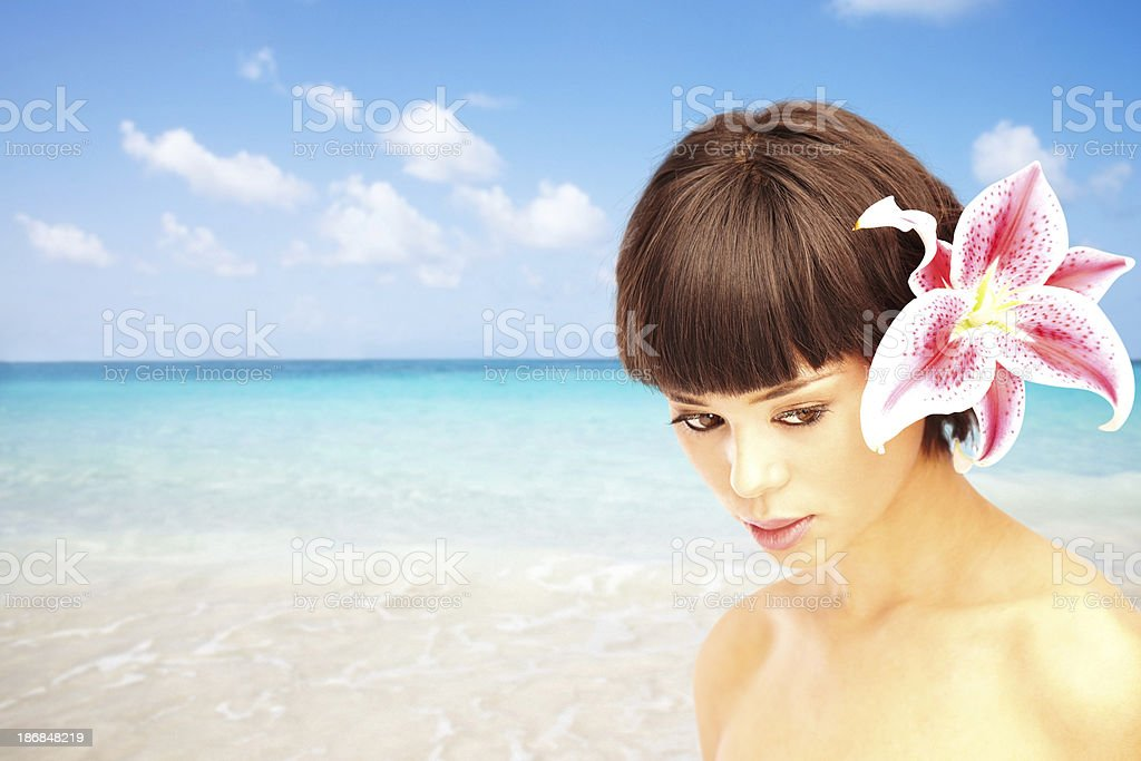 Beautiful woman with flower in her hair by ocean stock photo