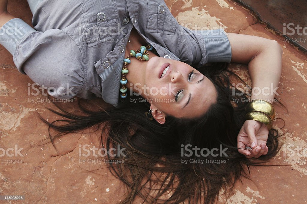 Beautiful woman with flowing hair laying on a rock stock photo