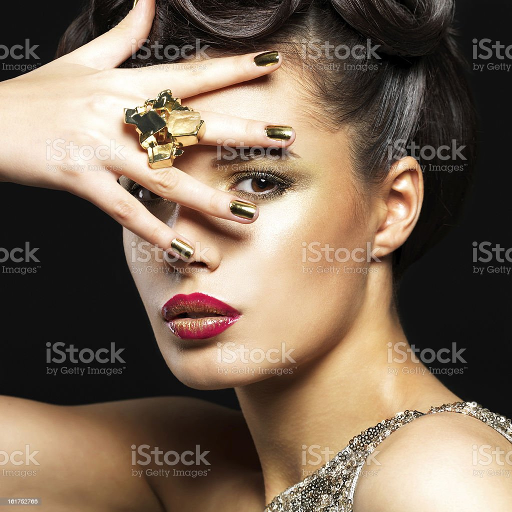 Beautiful woman with golden nails and style makeup royalty-free stock photo