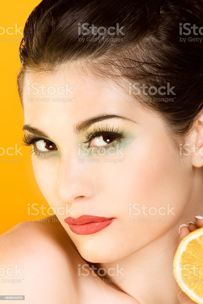 Beautiful woman with half of lemon looking at you royalty-free stock photo