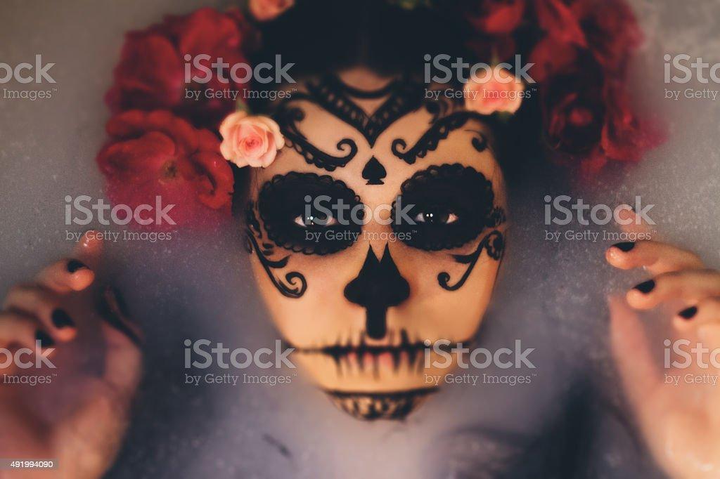 Beautiful woman with halloween sugar skull make-up stock photo