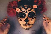 Beautiful woman with halloween sugar skull make-up