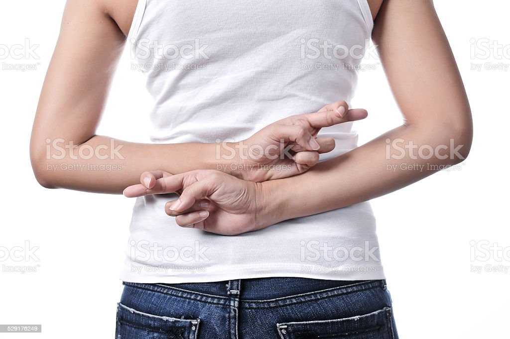 Beautiful woman with her fingers crossed behind her back stock photo