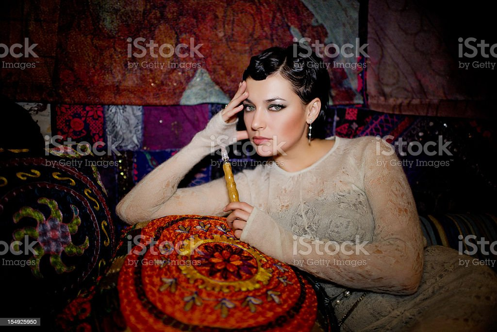 Beautiful Woman with hookakh in oriental decorated room stock photo