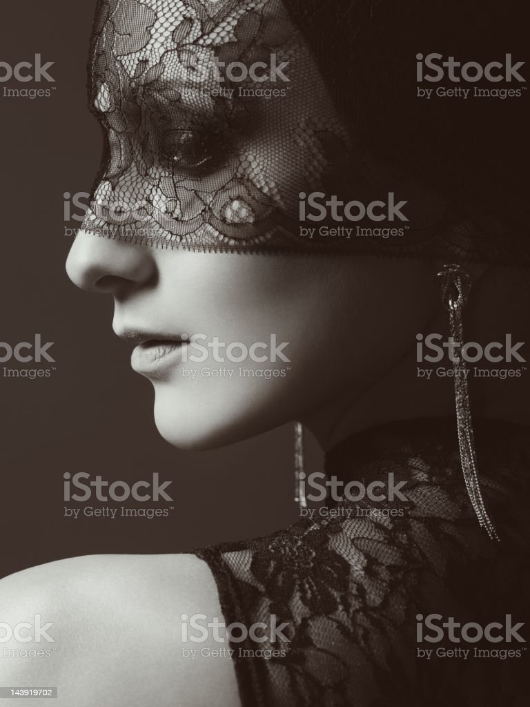 Beautiful woman with lace mask over her eyes stock photo