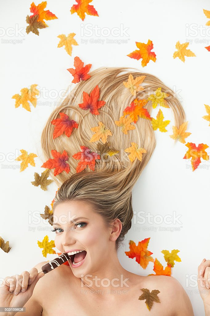 Beautiful woman with leaf and eating ice cream stock photo