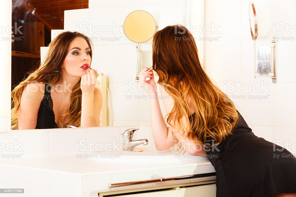 Beautiful woman with lipstick in bathroom. stock photo