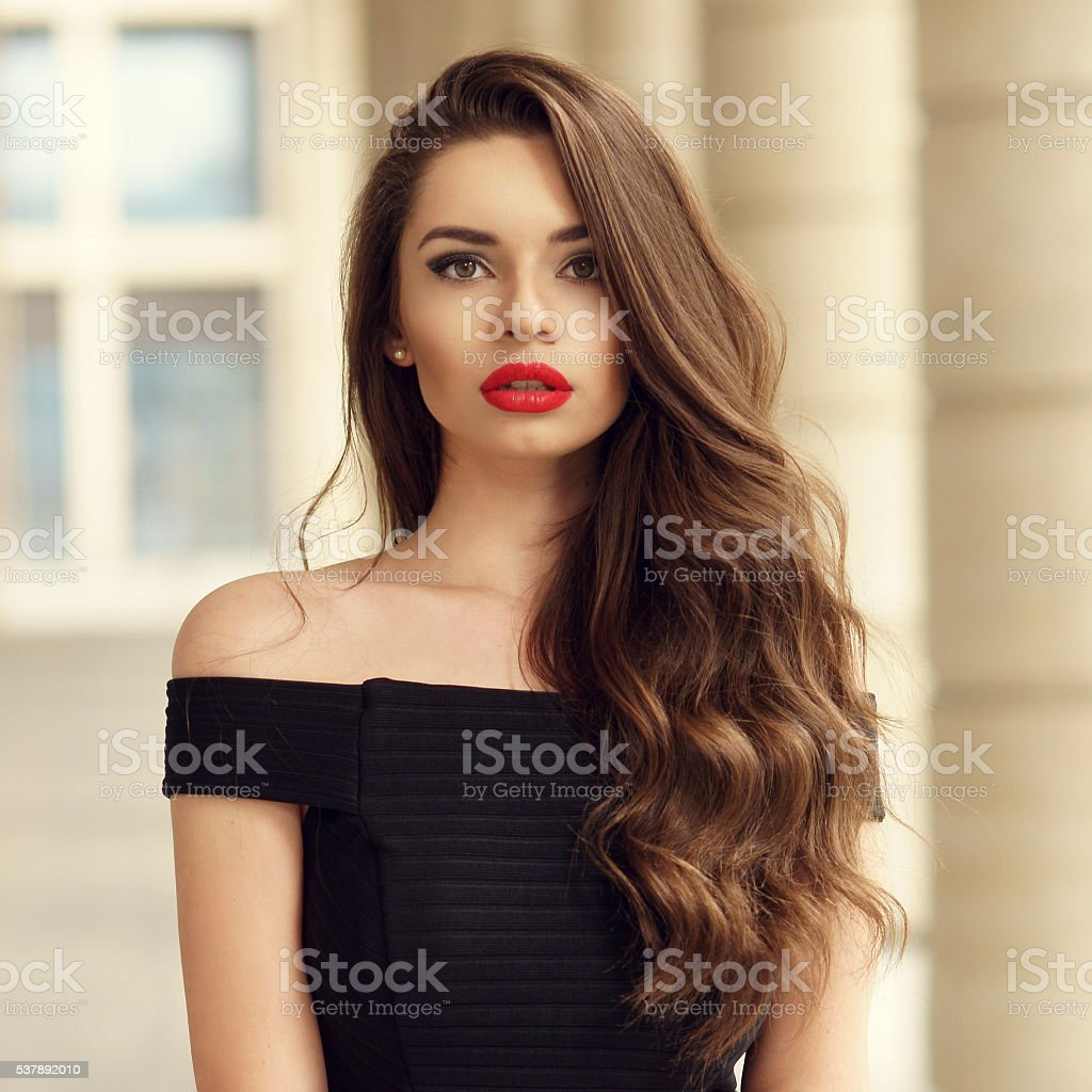 Close up portrait of young beautiful woman with long brunette curly...