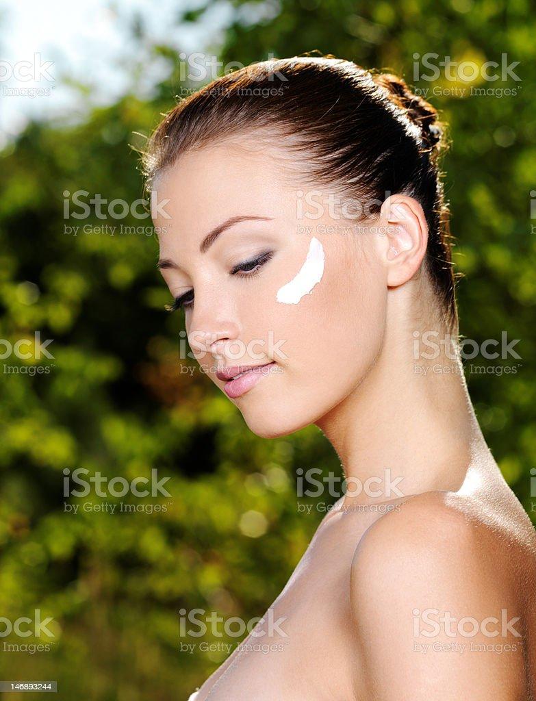 Beautiful woman with moisturizer cream on cheek royalty-free stock photo