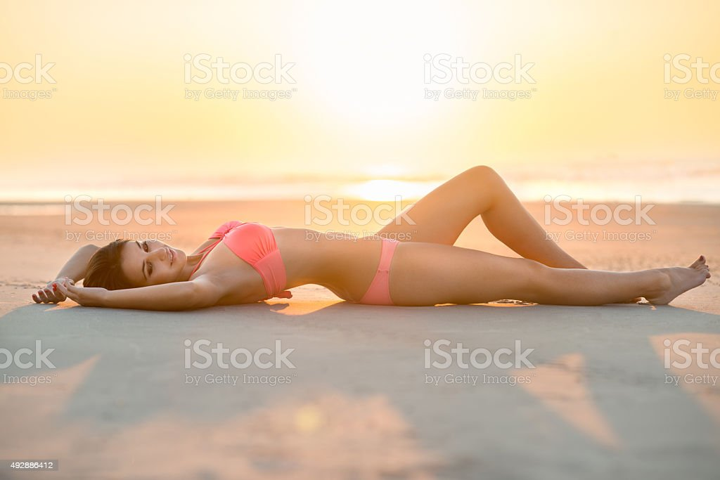 beautiful woman with perfect body lying on the beach stock photo