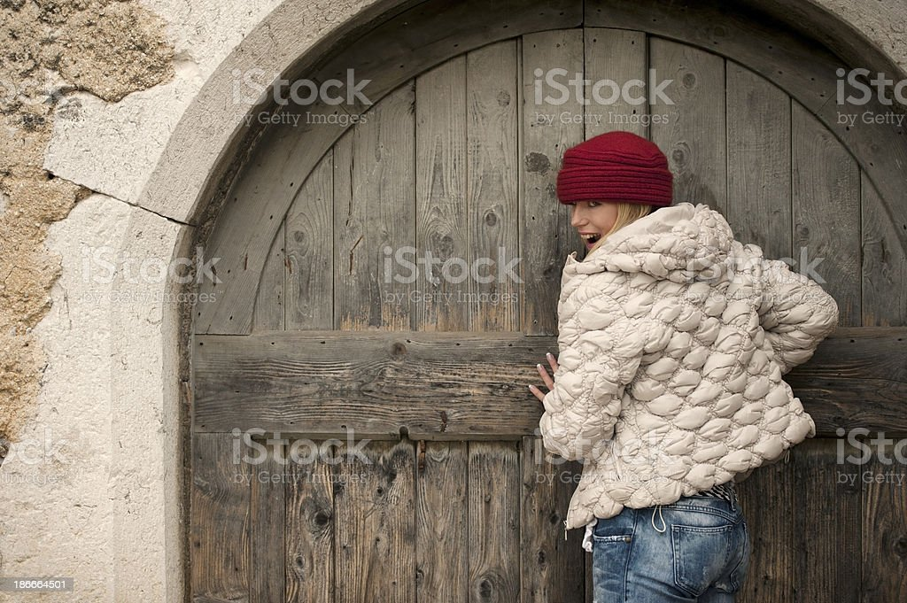 Beautiful Woman with Red Woolen Cap is Opening Home Door royalty-free stock photo