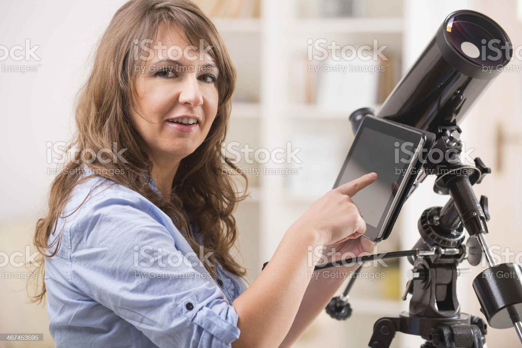 Beautiful woman with telescope and tablet royalty-free stock photo