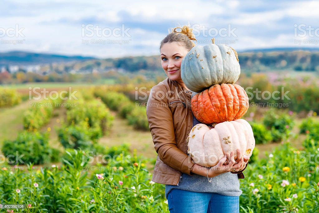 Beautiful woman with three huge pumpkins on farm stock photo