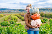 Beautiful woman with three huge pumpkins on farm