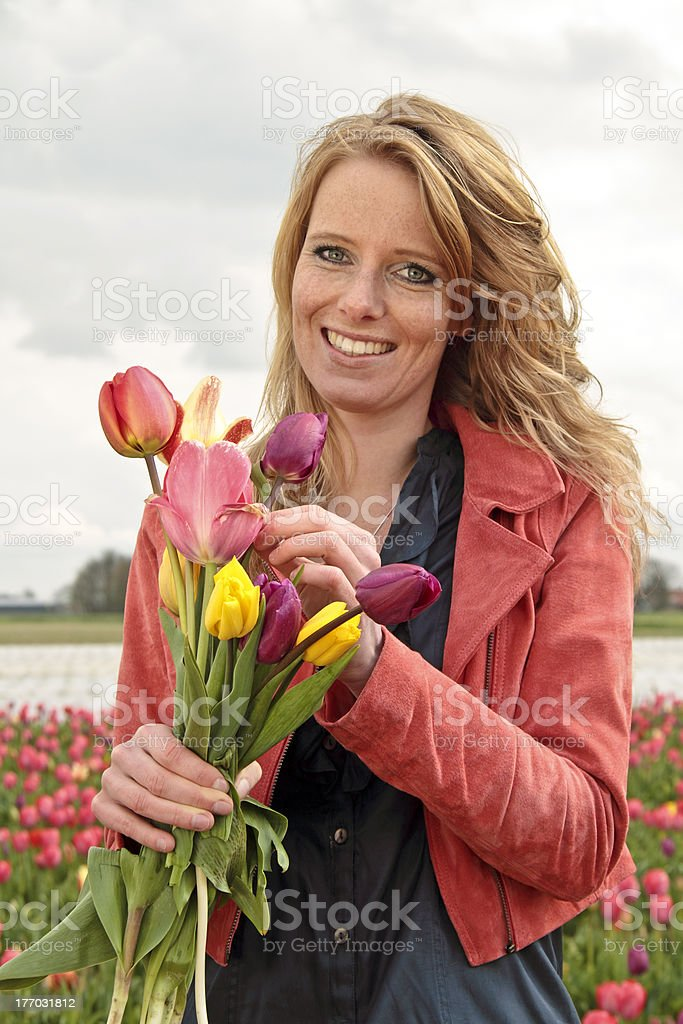 Beautiful woman with tulips in the fields royalty-free stock photo
