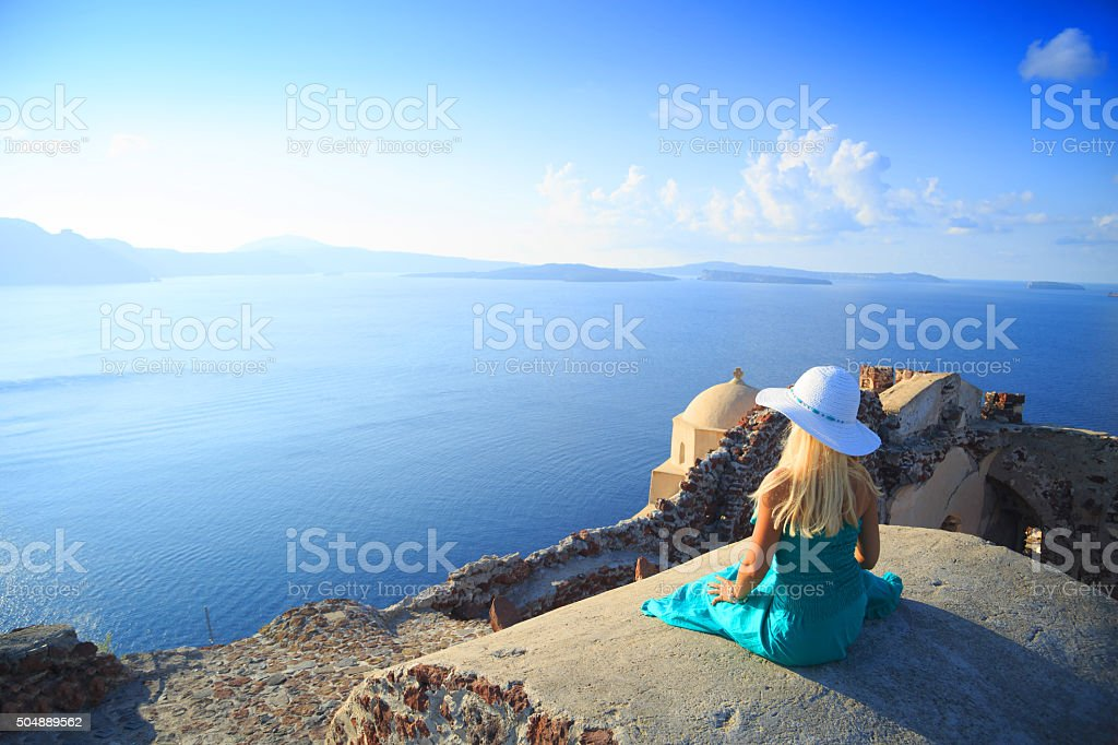 Beautiful Woman with turquoise dress in Santorini, Greece. stock photo