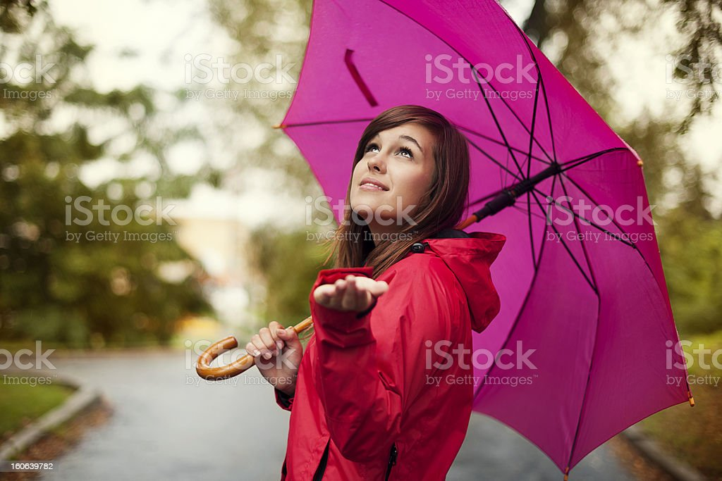 Beautiful woman with umbrella checking for rain stock photo