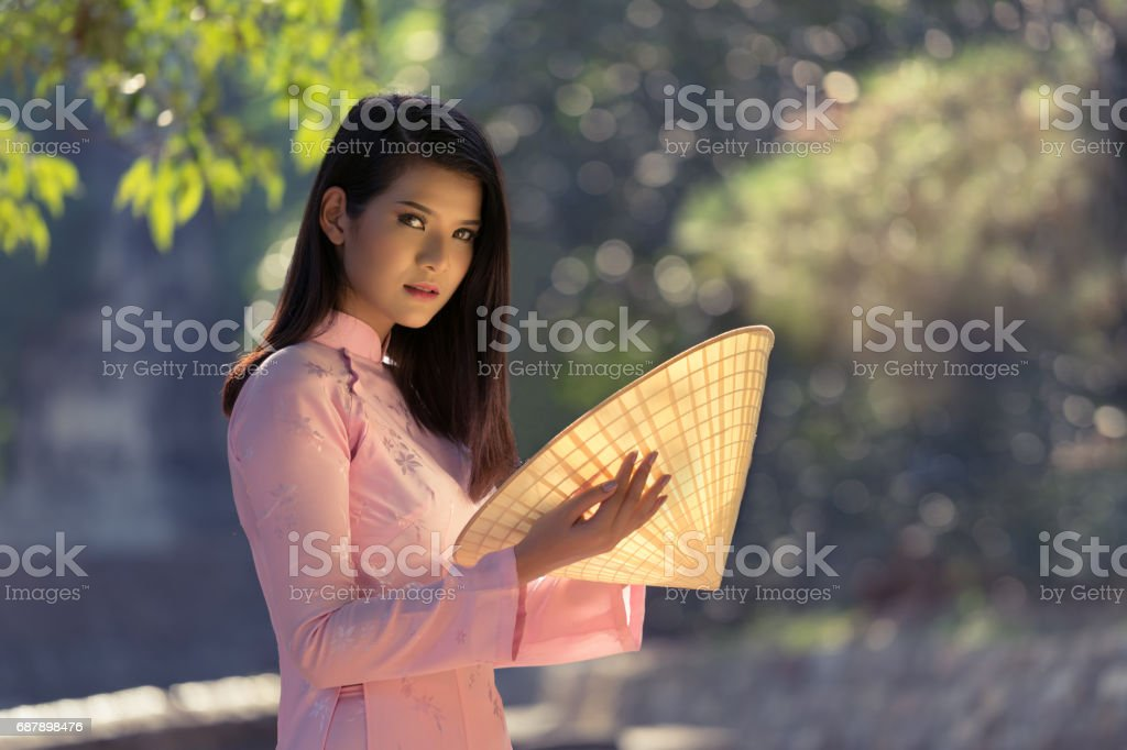 Beautiful woman with Vietnam culture traditional dress, Ao dai and holding straw hat. stock photo