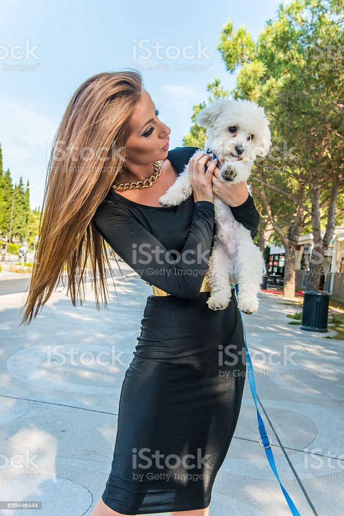Beautiful Woman with White Small Dog in Portorose, Slovenia, Europe stock photo