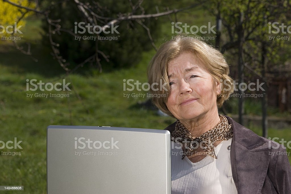 Beautiful woman working outdoors with a laptop royalty-free stock photo