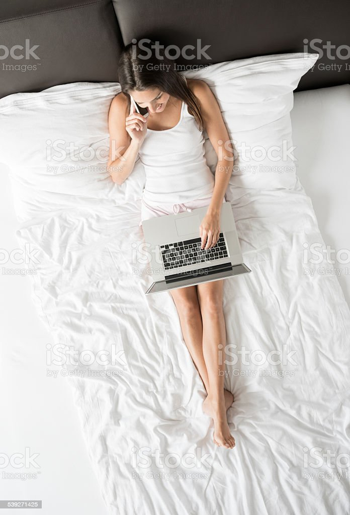Beautiful Woman working with Laptop and Phone in Bed stock photo