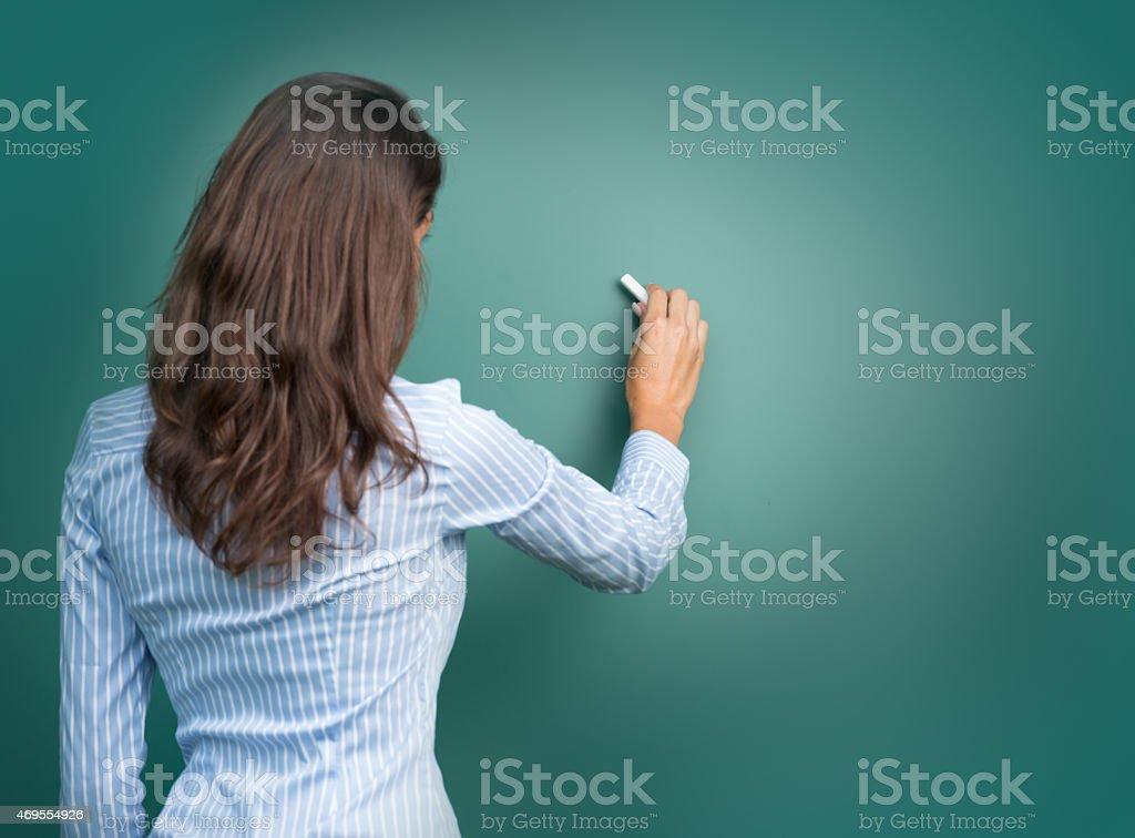 Beautiful Woman writing on Blackboard stock photo