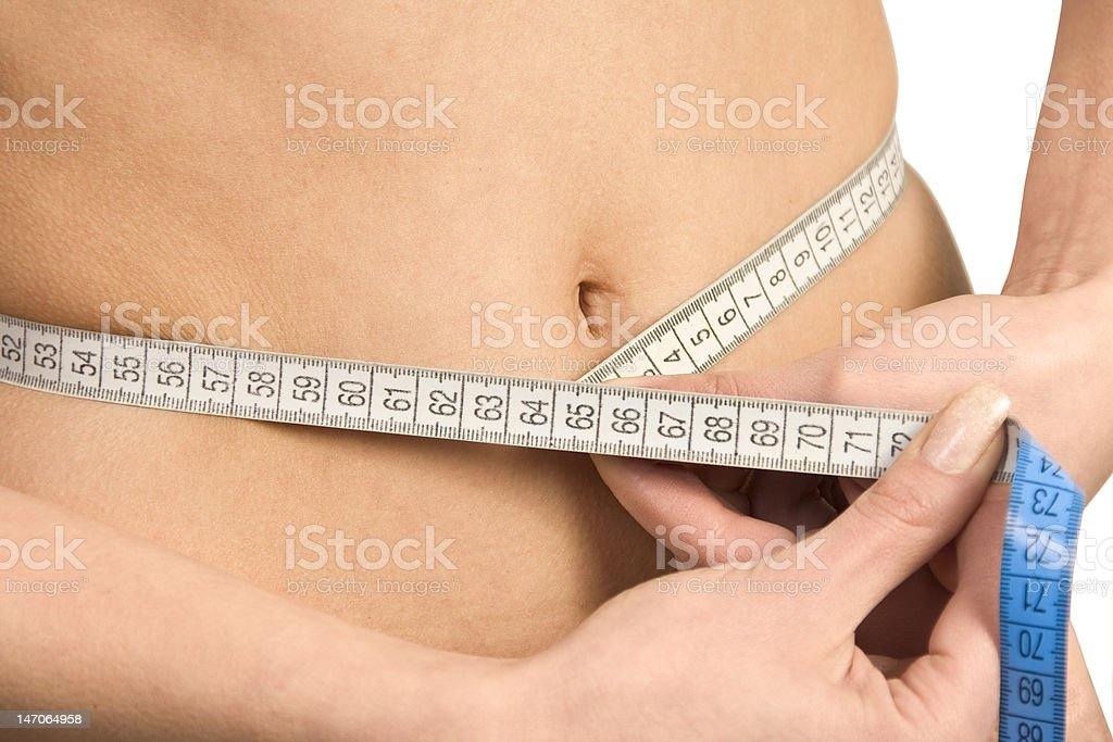 Beautiful woman's stomach with measure. royalty-free stock photo