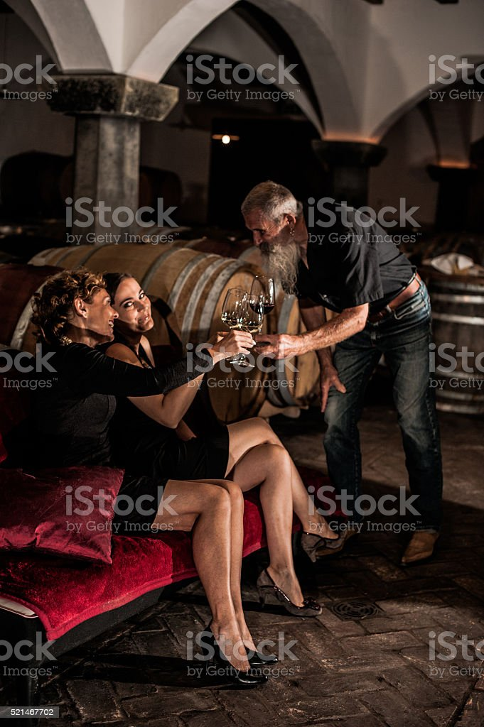 Beautiful Women and Senior Man in Old Wine Cellar, Europe stock photo