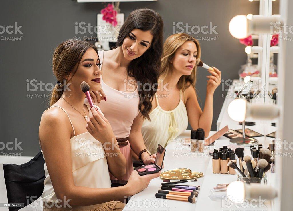 Beautiful women applying make-up in a beauty salon. stock photo