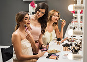 Beautiful women applying make-up in a beauty salon.