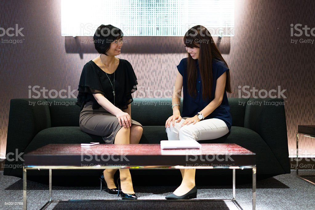 Beautiful women discussing in hotel lobby after business meeting stock photo