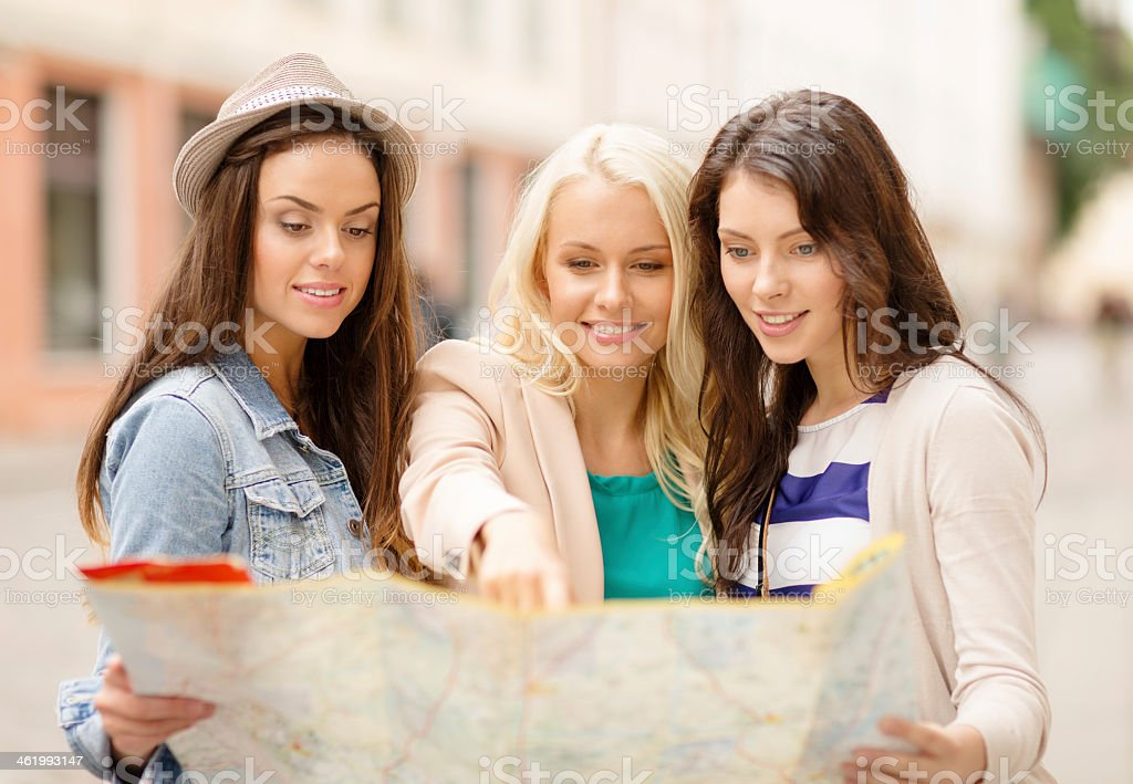 beautiful women looking at tourist map in city stock photo