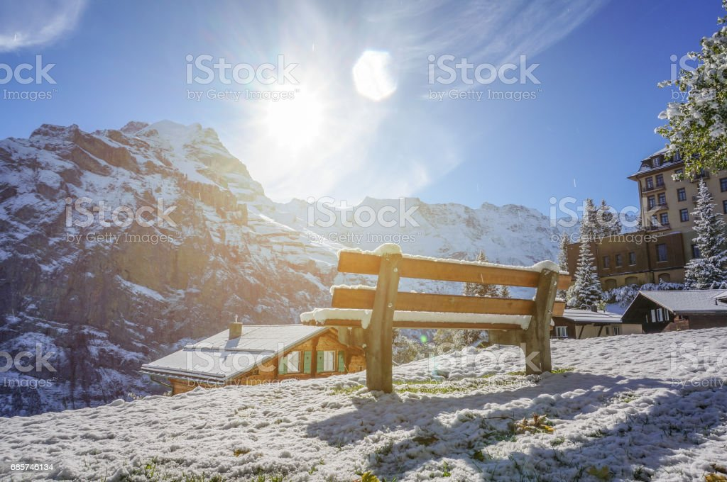 Beautiful wooden bench seating in snow mountain Alp sun shine daylight with artificial warm flare, Switzerland stock photo