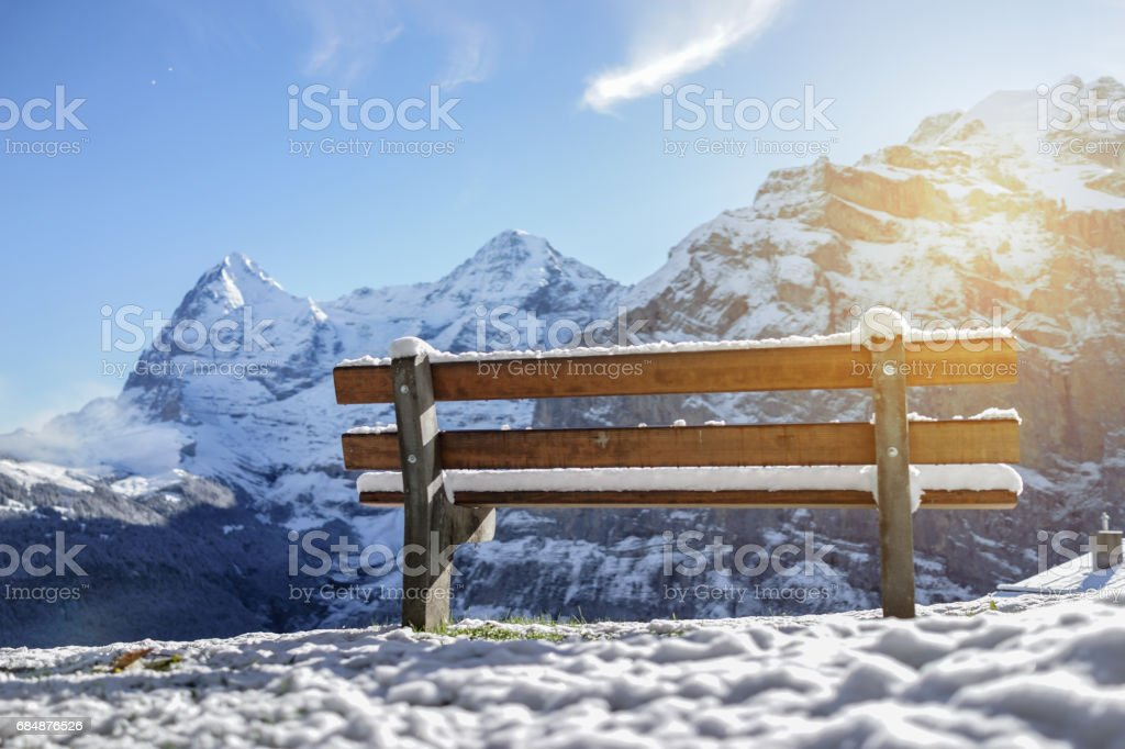 Beautiful wooden bench seating in snow mountain Alp sunrise with artificial warm flare, Switzerland stock photo