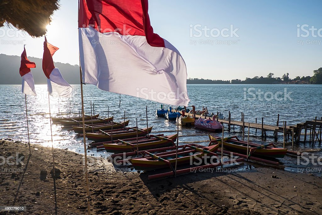 Beautiful wooden pier and Indonesia flag at sunrise stock photo