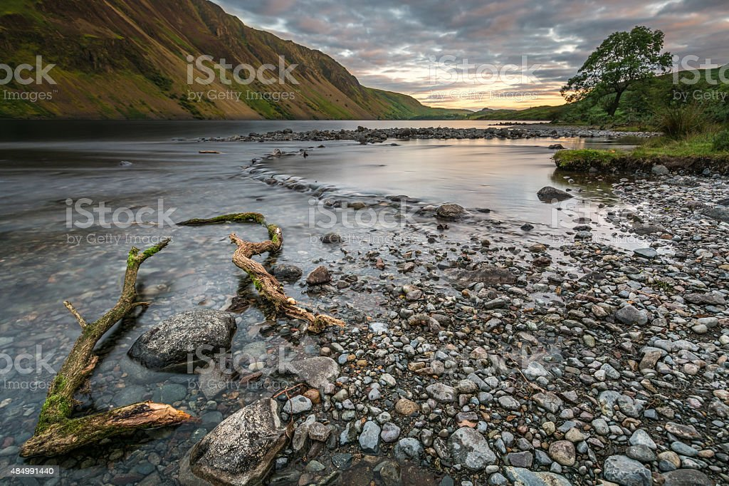 Beautiful Yellow Sunset With Rocks In Foreground At Wast Water. stock photo