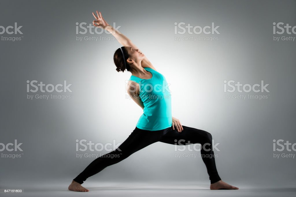 beautiful yoga lady standing in grey background stock photo